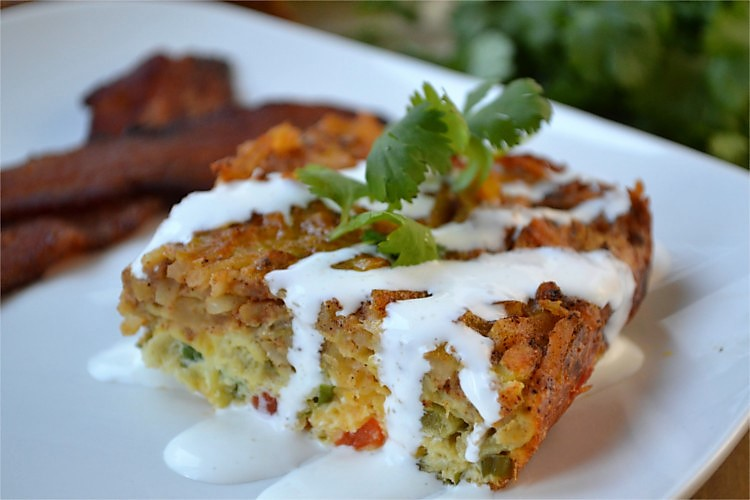 Mexican Breakfast Casserole - A deliciously simple egg and hash brown casserole with a crispy Mexican flavored crust covering layers of fluffy eggs, cheese, onions, peppers and green chiles.
